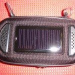 Case outside, showing the carabiners on top. The white dot on the left side of the solar panel is the blue 'charging' LED