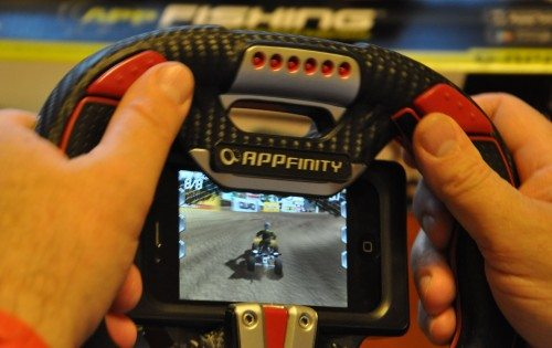 """The AppDriver lets you truly get the feel of driving games. The thumb buttons are matched with index finger triggers under the wheel. Note the small """"shelf"""" over the top of the screen, which hides the touch pads."""