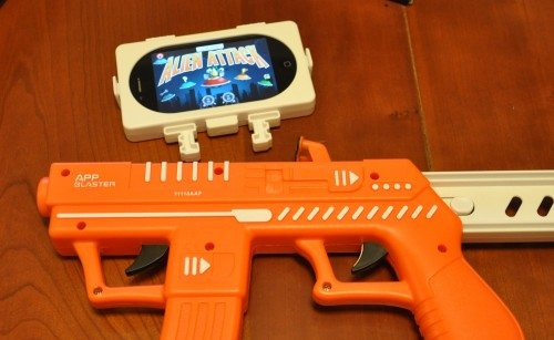 AppBlaster, showing the device holder with an iPhone 4s. This clips onto the barrel in the slot just forward of the rear trigger, so that the two tap pads can touch the screen. Note the locking sliders on the side to secure the device holder onto the controller.
