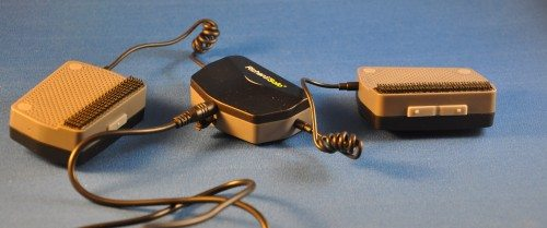 The FreeWheelin' consists of three devices connected by curly cables. The left box has a single button for on/off and connection, the right box has volume up/down buttons.