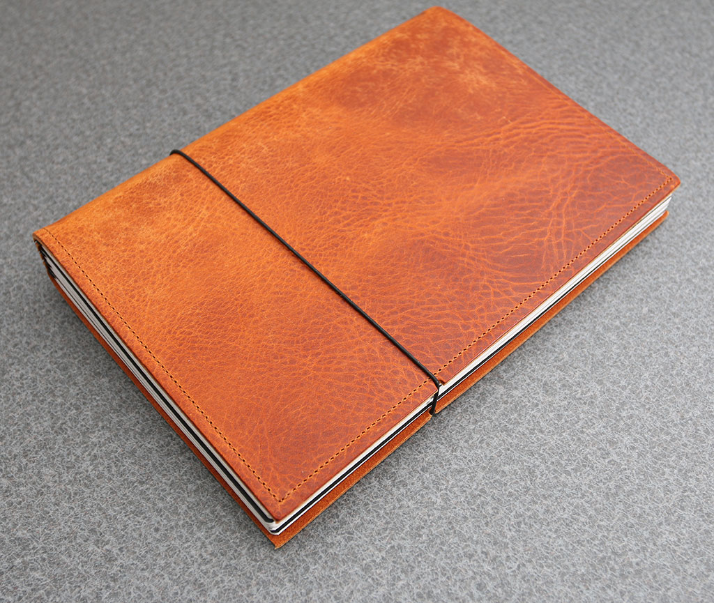 x17 and x47 notebooks review small slots on the edge of the cover keep the tight band from marring the leather